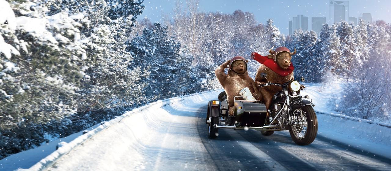 Animation von Bulle und Bär, die auf einem Motorrad sitzend, rasant durch die Winterlandschaft fahren.