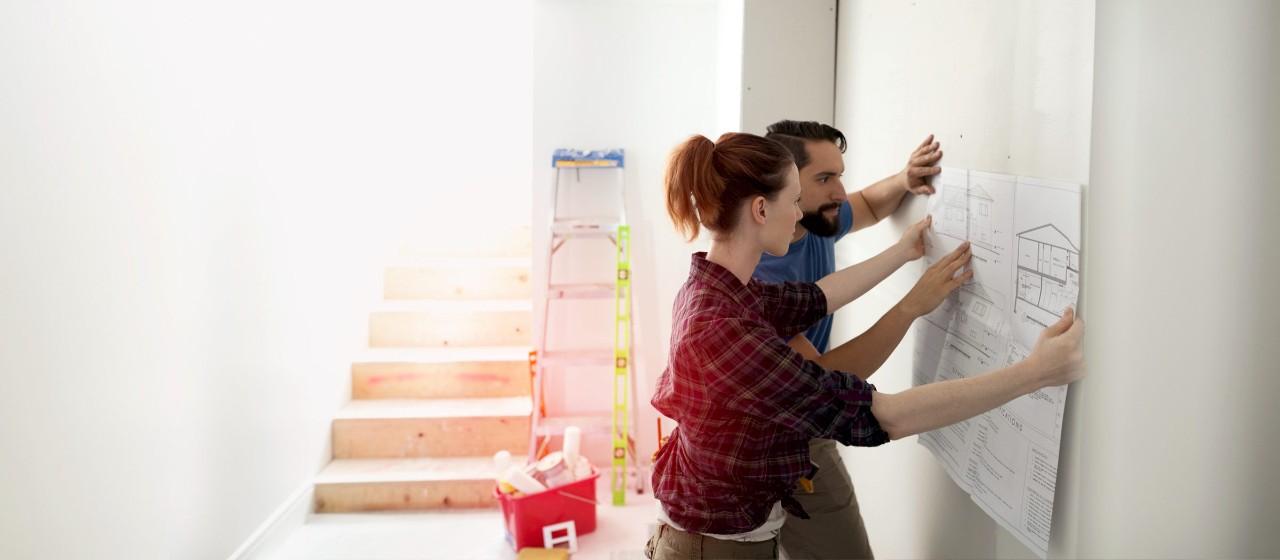 Kinderzeichnung eines Hauses mit umherliegenden Buntstiften.