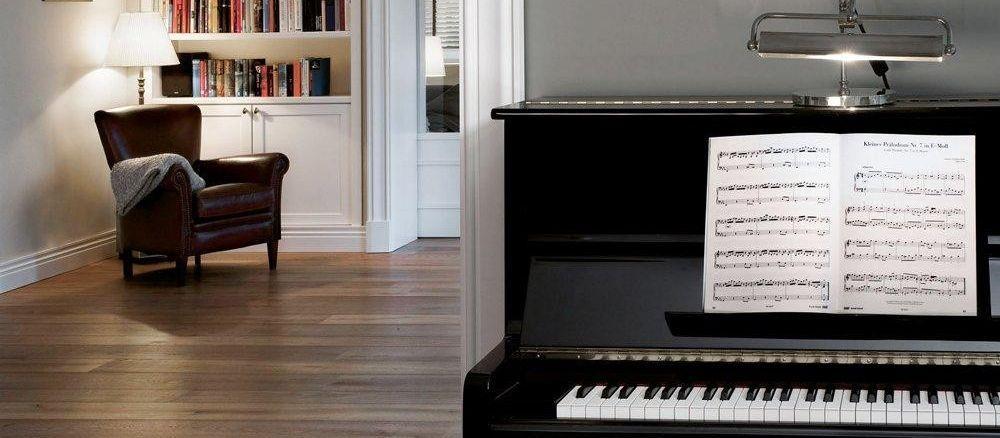 Blick in einen edel eingerichteten Wohnraum mit Klavier, Bücherregal und Lederstuhl.